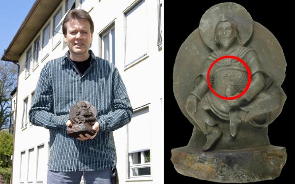 El geólogo Elmar Buchner sostiene la estatua
