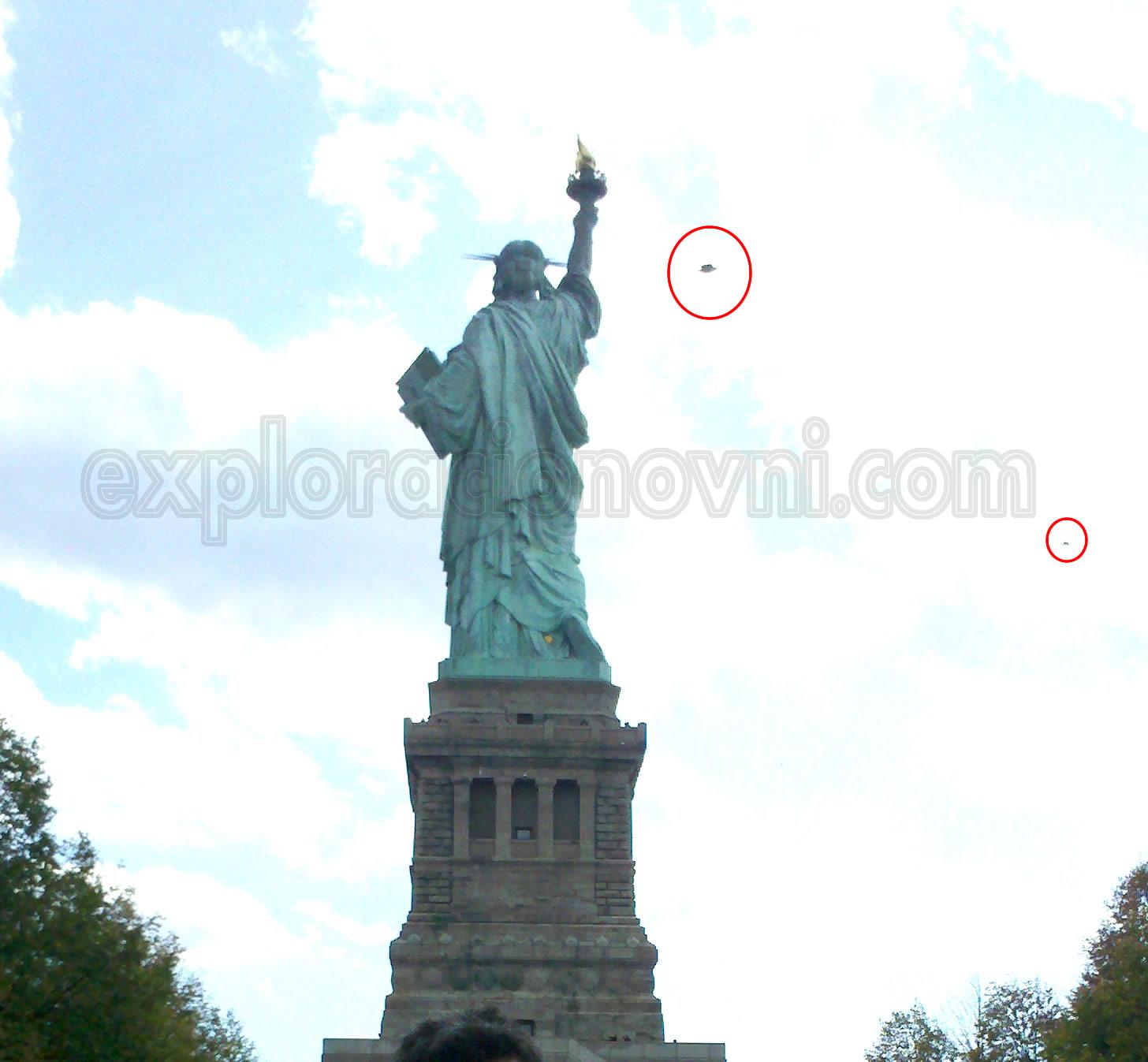 Imagen tomada a la Estatua de la Libertad y que muestra una anomalía en la parte superior, la forma es como la clásica forma de un OVNI, pero no posee un contraste definido. También puede verse una mancha de menor tamaño más abajo en la parte derecha.