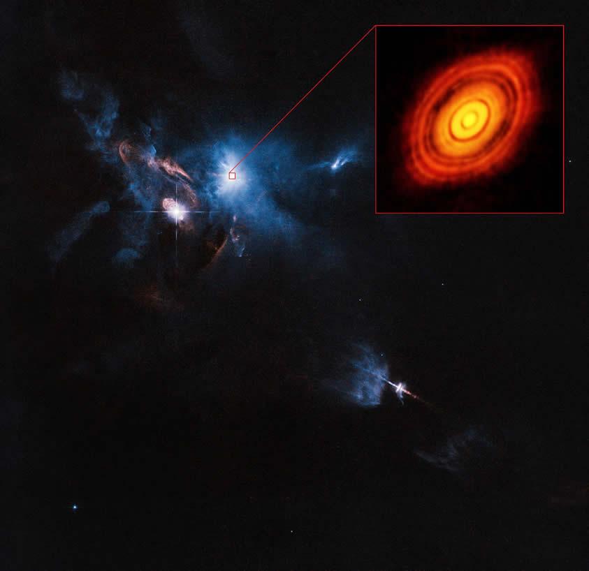 Esta es una composición de imágenes que nos muestra a la joven estrella HL Tauri y sus alrededores. Está hecha con datos obtenidos por ALMA (ampliada en el marco superior derecho) y por el telescopio espacial Hubble de NASA/ESA (resto de la imagen). Esta es la primera imagen de ALMA en la que se supera la nitidez que suelen alcanzar las imágenes del Hubble. Crédito: ALMA (ESO/NAOJ/NRAO), ESA/Hubble and NASA