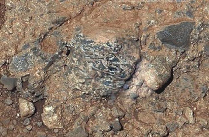 Clast ígnea llamada Harrison incrustado en una roca en el cráter Gale, Marte, Muestra cristales alargados de feldespato de tonos claros.