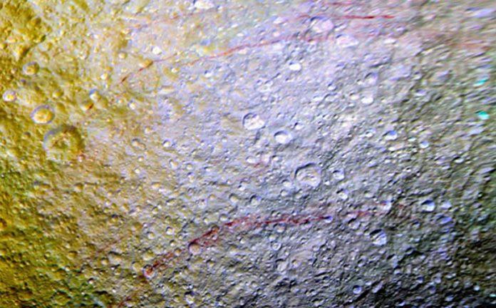 Esta imagen con color mejorado muestra los impresionantes arcos rojos que cortan la superficie de hielo de Tetis.