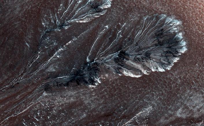 Esta nueva imagen del Orbitador de Reconocimiento de Marte de la NASA muestra la escarcha formada en los barrancos en uno de los cráteres de las llanuras del norte de Marte.