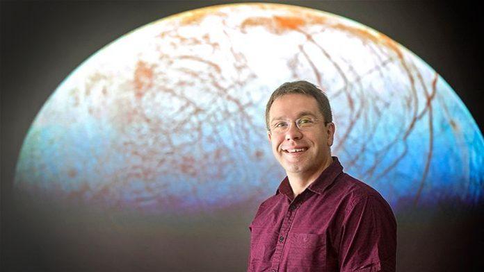 El Dr Jonti Horner delante de una imagen del satélite de Júpiter, Europa.